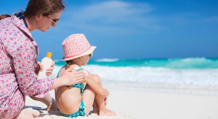 Мама наносит солнцезащитный крем ребенку на пляже