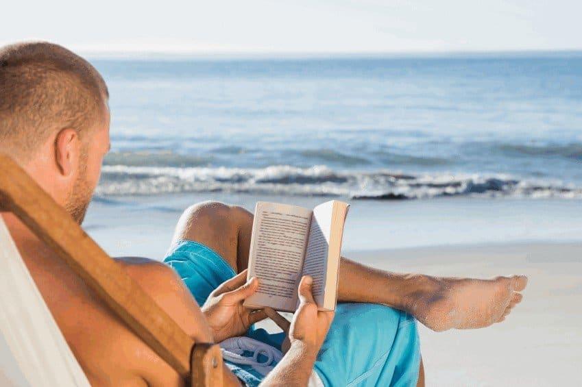 Мужчина с книгой на пляже