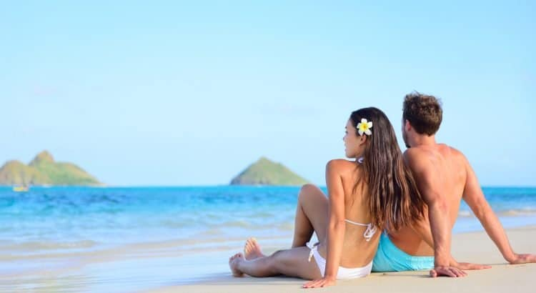 Пара сидит на пляже на Гавайи
