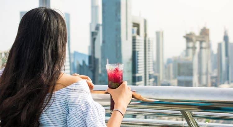 Девушка с напитком на фоне Дубаи