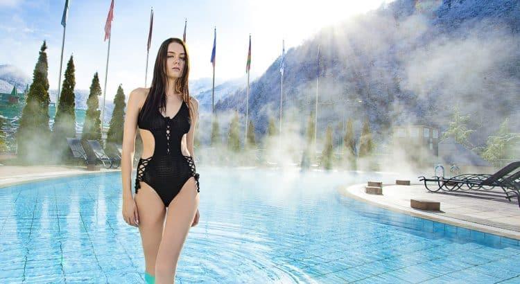 Девушка в бассейне на фоне гор