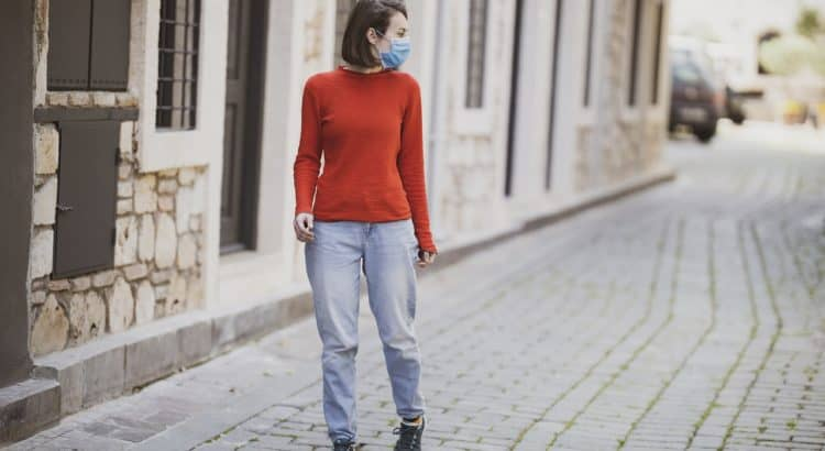 Женщина в маске на пустых улицах города